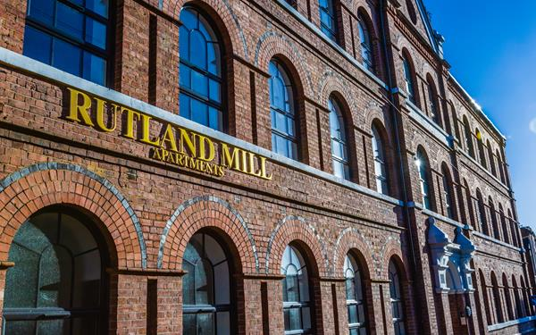 Exterior shot of Rutland Mills apartments with the sign