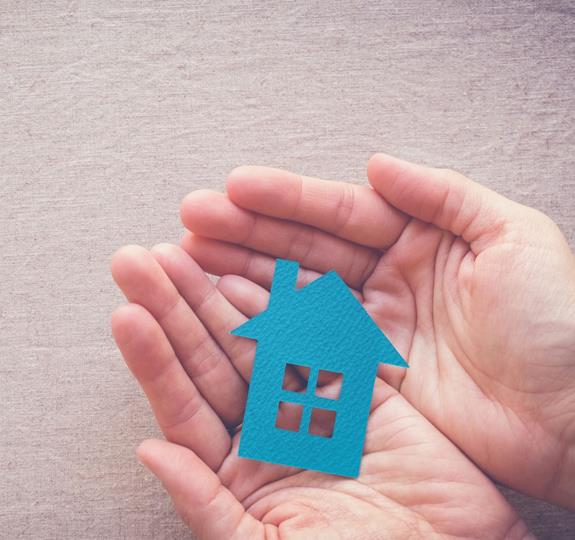 A small blue cut-out shape of a house being held in someone's open hands
