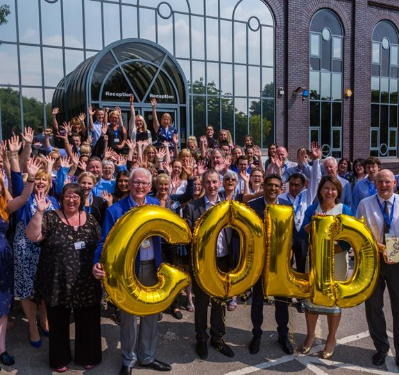 Staff outside Asher House holding gold balloons spelling-out Gold