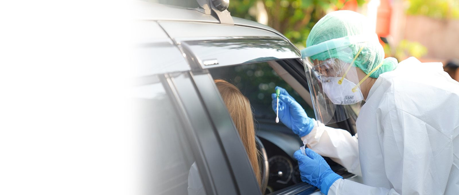 Someone in PPE preparing to swab a woman in a car (1)